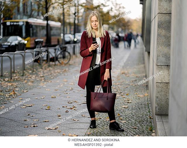 Blond businesswoman using smartphone in the city