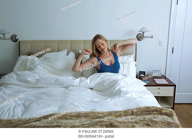 Woman sitting up and stretching arms in bed