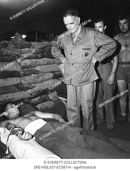 Admiral William Halsey visiting a sandbagged hospital dugout at Bougainville. The soldier is receiving a saline injection after an appendectomy in South Pacific...