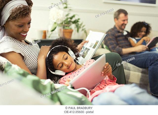 Mother cuddling daughter with headphones using digital tablet