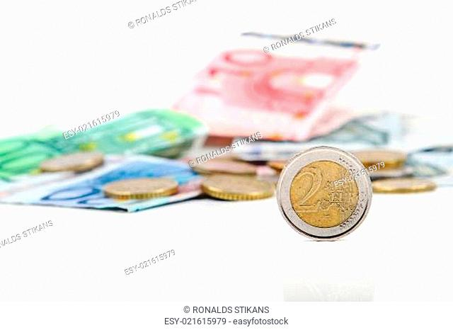 two euro coin with other euro coins and banknotes in background