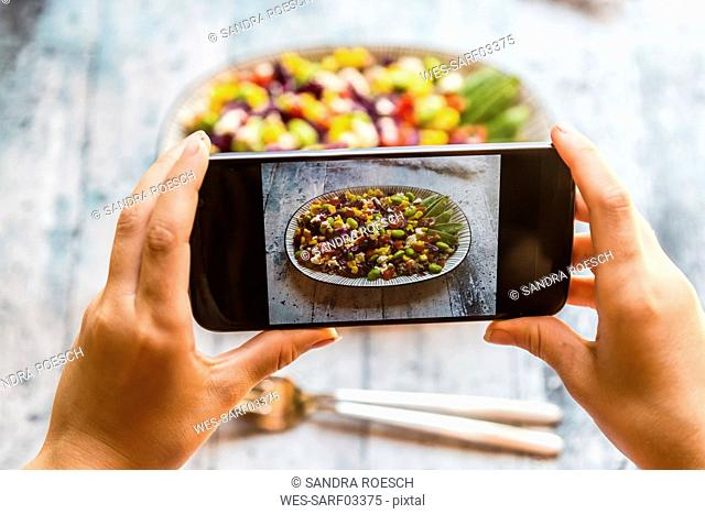 Girl taking picture of Quinoa salad with smartphone, close-up