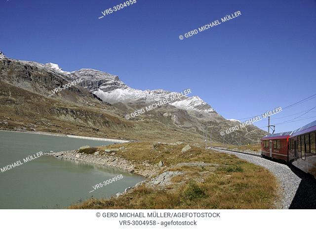 "Lake Bianco/Bernina: The """"Rhätische"""" railway crossing the Unesco World Heritage region in the Swiss alps"
