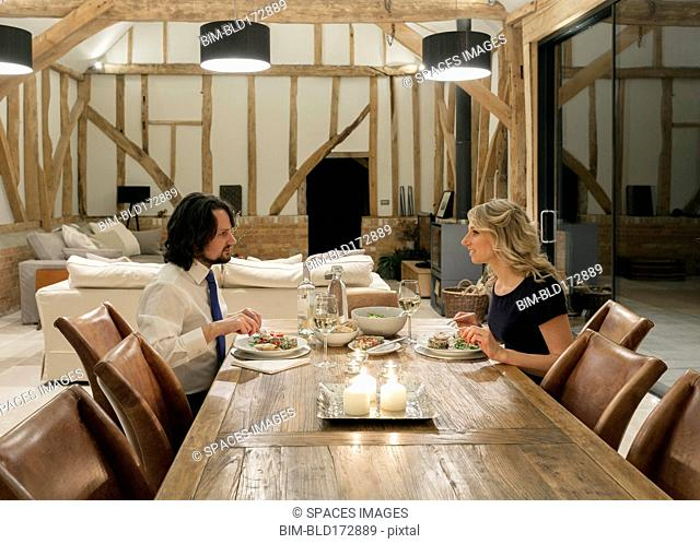 Caucasian couple in dining room of converted barn home