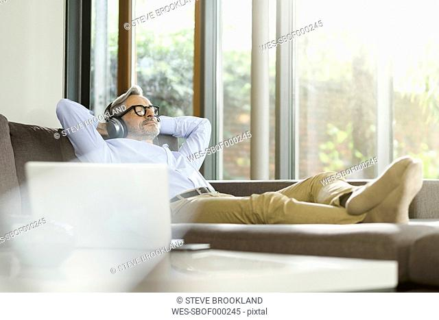 Man relaxing on the couch listening music with headphones