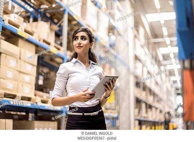 Woman with tablet in factory storehouse looking around