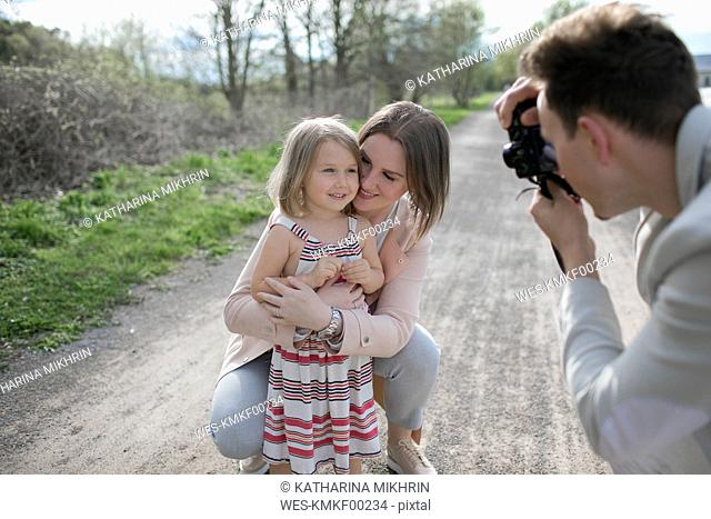 Young man taking photo of his family with camera