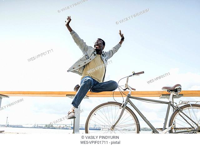 Young man with bicycle, sitting on railng by the sea, pretending to fly