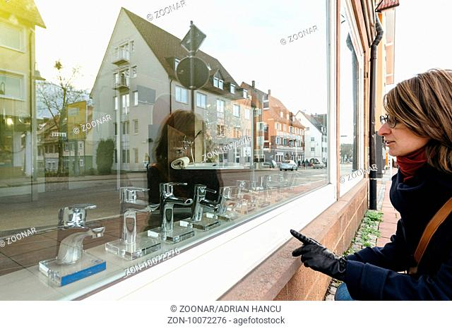 Woman chossing in store windows the new faucet for her bathroom kithcne