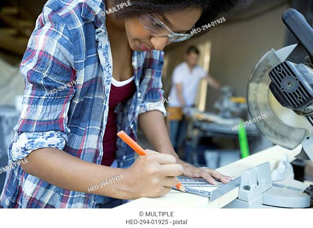 Woman marking wood for home improvement project at table saw