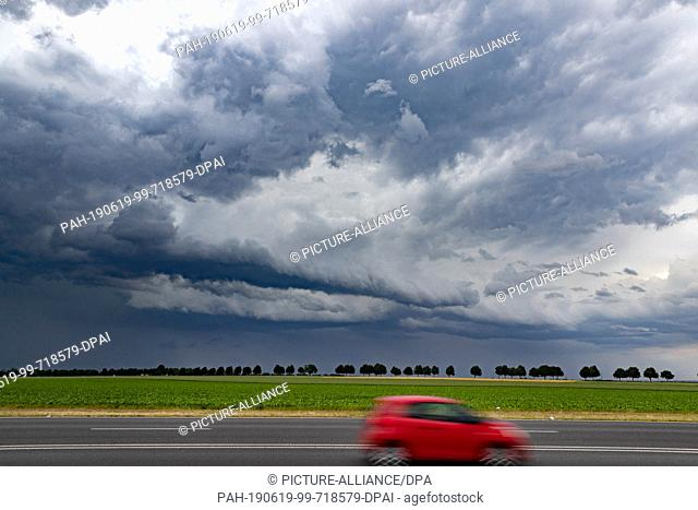 19 June 2019, North Rhine-Westphalia, Bergheim: A red car is driving on a federal highway. In the background dark thunderclouds can be seen
