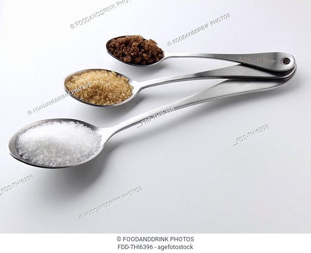 Granulated demerara and dark brown sugar in spoons