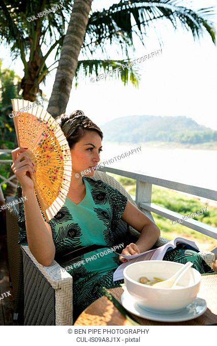 Woman sitting in cafe holding fan