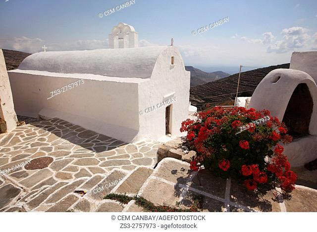 White chapel in the old town Chora or Chorio with geranium flowers in the foreground, Sikinos, Cyclades Islands, Greek Islands, Greece, Europe