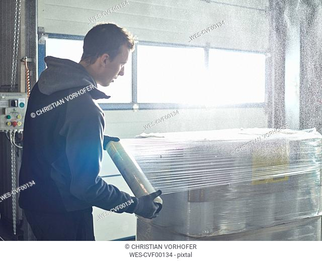 Worker closing freight with foil