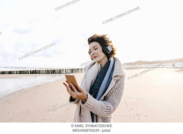 Woman on the beach with cell phone and headphones