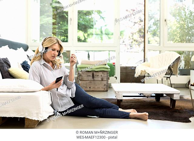 Relaxed woman at home listening to music