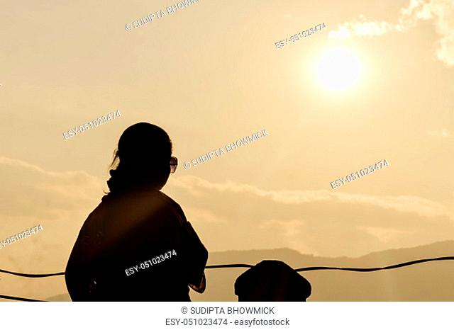 Portrait of young woman as silhouette by the evening sun looking into sky at horizon. Stress free concept. Empty copy space room for text in right side