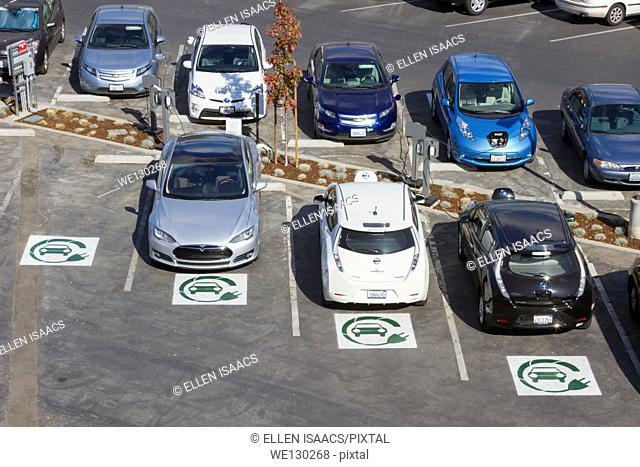 Different types of plug-in electric cars parked at EV charging stations in a company parking lot