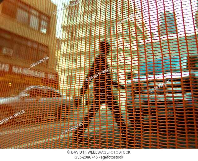 Net against man crossing the road in in New York, New York