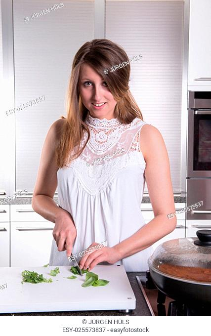 attractive young woman is cutting basil