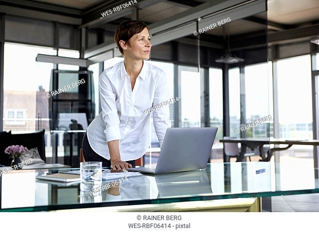 Businesswoman standing at glass table in office with laptop looking sideways