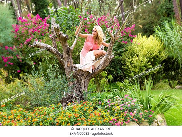 romantic young woman sitting on tree in park with flowers