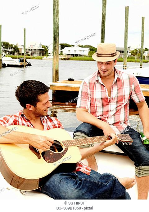 Two adult brothers playing acoustic guitar on marina motorboat