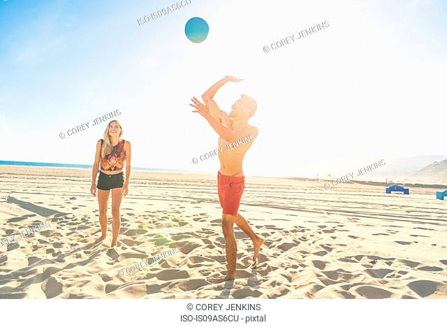 Young man on beach about to to strike volleyball