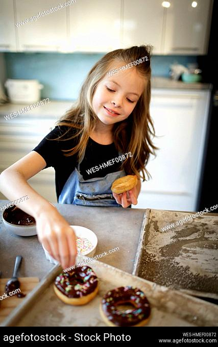 Portrait of smiling girl decorating home-baked doughnuts with sugar granules