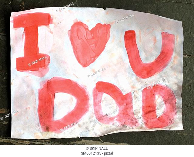 A child's hand painted sign saying I love you dad