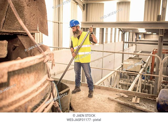 Man working in factory hall at giant concrete mixer