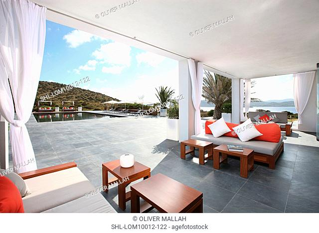 Covered sitting area on patio near pool