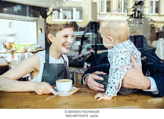 Waitress serving coffee to smiling customer with baby in cafe