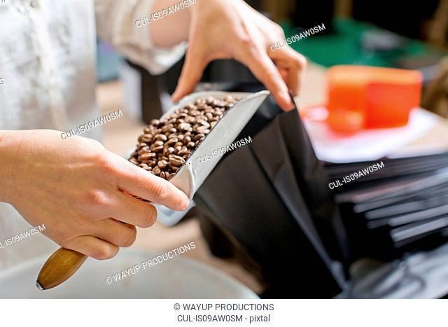Coffee seller filling bag with coffee beans