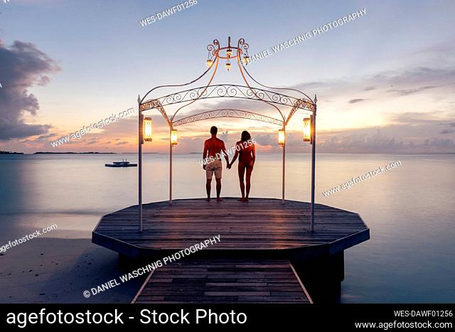 Couple standing on jetty at the sea at sunset, Maguhdhuvaa Island, Gaafu Dhaalu Atoll, Maldives