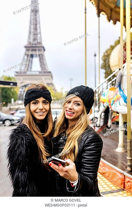 France, Paris, two best friends with a carousel and the Eiffel Tower in the background