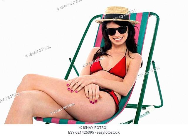 Sexy bikini model relaxing on deckchair