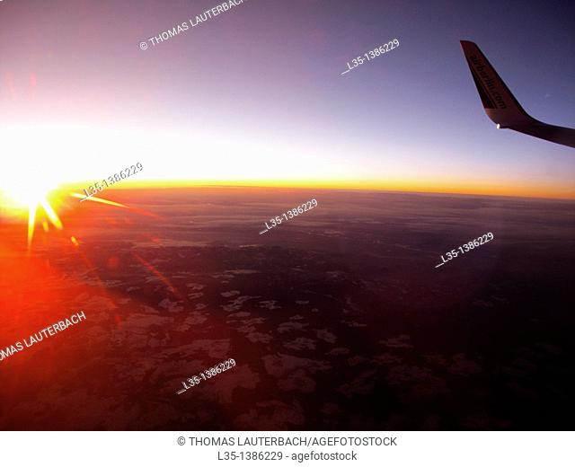 Sunrise over the clouds, wing tip position light and the rising sun