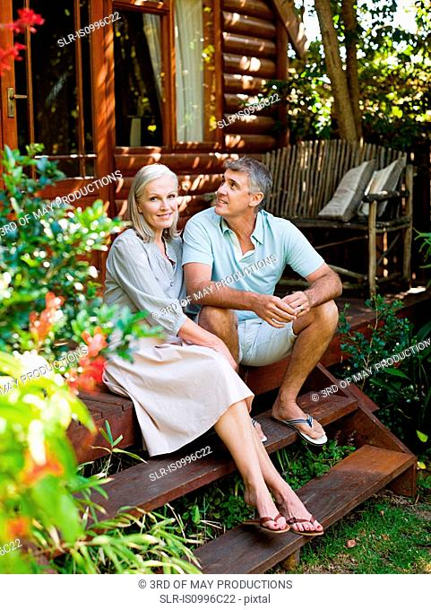 Couple sitting on porch steps in garden