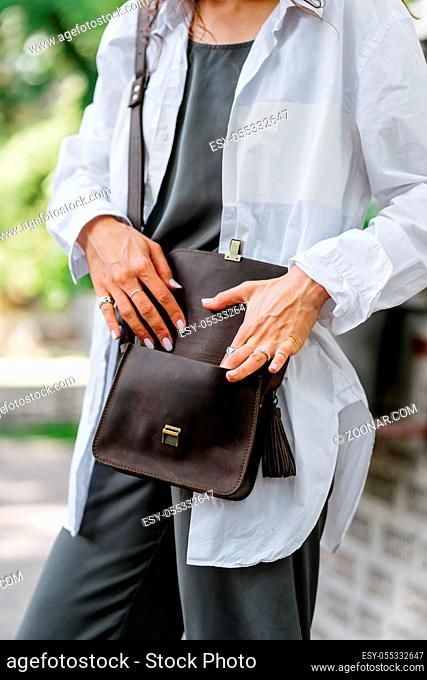 Fashionable, beautiful, women's bag from a close angle. Girl posing for the camera with a female bag