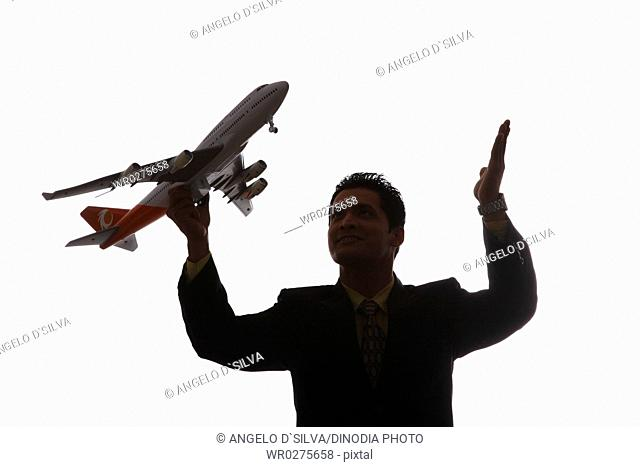 Businessman in silhouette holding passenger aeroplane in flying angle in one hand and raised other hand MR703T,NO PR