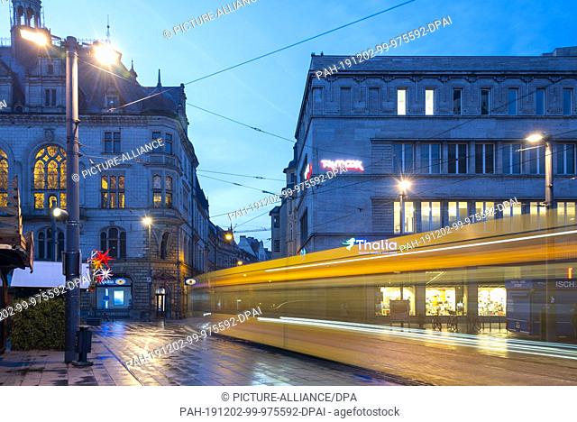 22 November 2019, Saxony-Anhalt, Halle: In the early morning, a tram crosses the market square of Halle. The traditional Christmas market takes place on the...