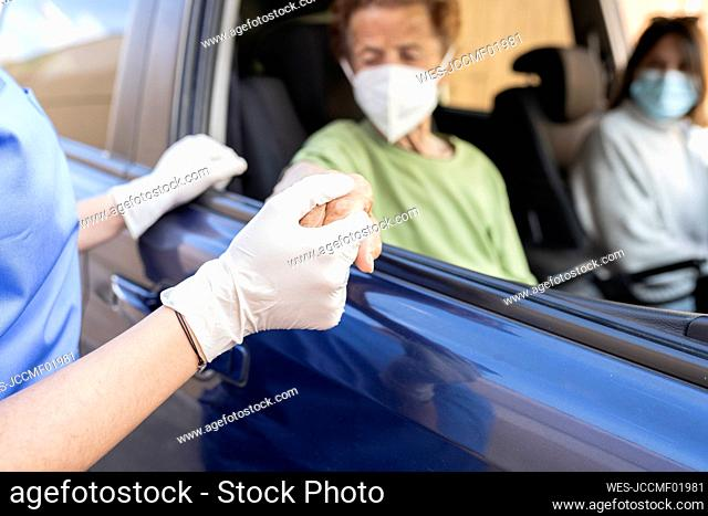 Female healthcare worker holding hand of senior patient sitting in car