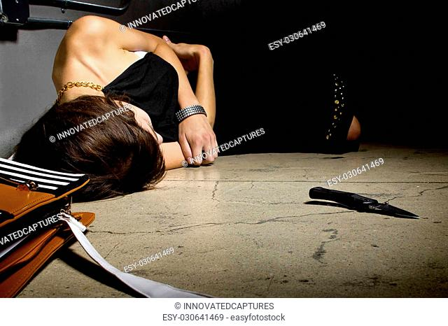 female laying dead on a street alley with a knife murder weapon