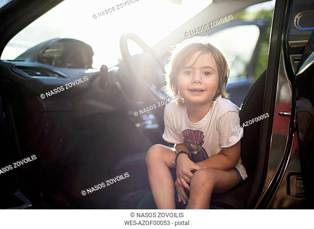 Portrait of little boy sitting on driver's seat in a car at backlight