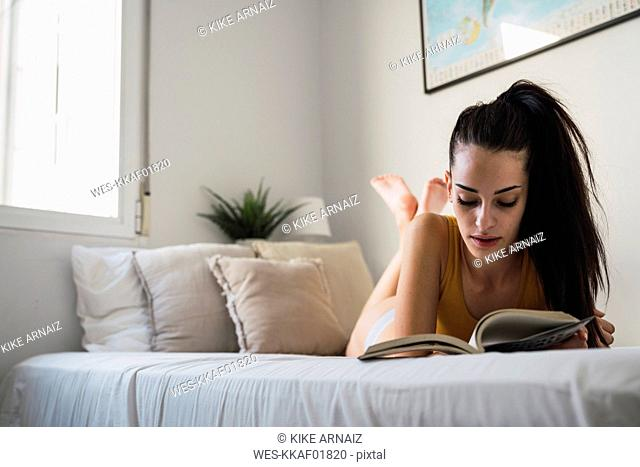 Beautiful young woman lying on bed at home reading a book
