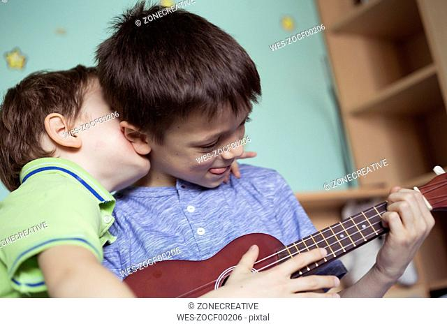 Boy playing ukulele while his little brother embracing him