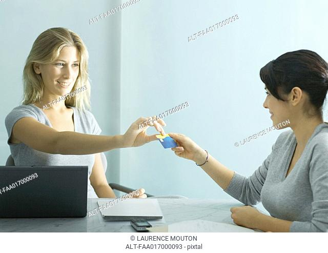 Young female professional handing teenage girl a card