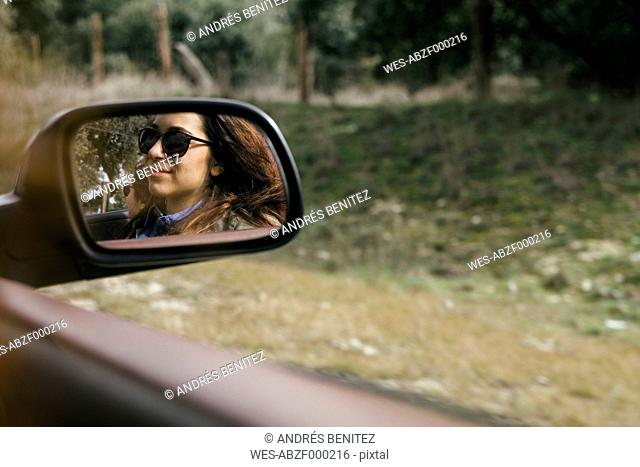 Reflection of young woman in wing mirror of convertible car